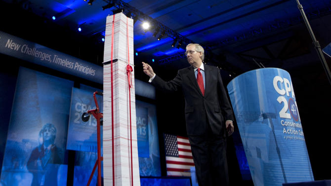 """FILE - In this March 15, 2013, file photo the Senate Minority Leader, Republican Mitch McConnell of Kentucky, points to a 7-foot stack of """"Obamacare"""" regulations to underscore his disdain during the 40th annual Conservative Political Action Conference in National Harbor, Md.  McConnell said Democrats have been predicting for years that Americans would learn to love the health care overhaul and that has not happened. """"I agree that it will be a big issue in 2014,"""" he said. """"I think it will be an albatross around the neck of every Democrat who voted for it. They are going to be running away from it, not toward it."""" (AP Photo/Manuel Balce Ceneta, File)"""