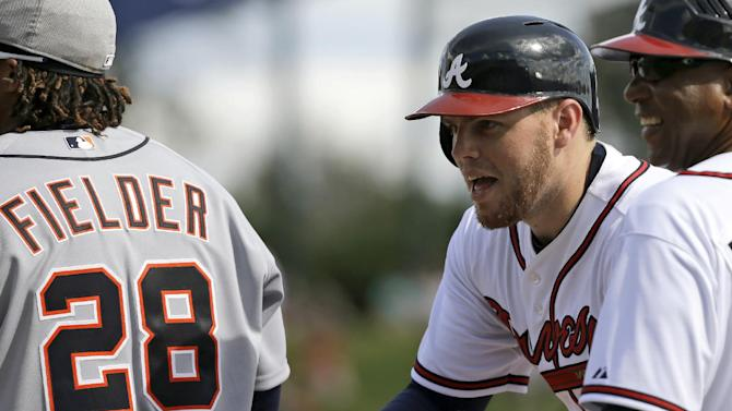 Atlanta Braves' Freddie Freeman, center, reacts after getting the first hit of the game as Detroit Tigers first baseman Prince Fielder (28) stands near him during an exhibition baseball game, Friday, Feb. 22, 2013, in Kissimmee, Fla. Braves first base coach Terry Pendleton is right. (AP Photo/David J. Phillip)