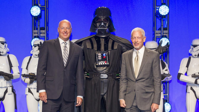 IMAGE DISTRIBUTED FOR DISNEY CONSUMER PRODUCTS - Disney Consumer Products President, Bob Chapek, left, and Lucasfilm Executive Vice President Howard Roffman pose with Darth Vader and 20 Stormtroopers as they take over the stage during a private Disney event at the Licensing Expo, Monday June 17, 2013 at the Mandalay Bay Convention Center in Las Vegas. This surprise grand finale, presented to more than 1,500 licensees, demonstrates a new era of merchandising potential for Disney Consumer Products' robust franchise portfolio, which now includes the Star Wars franchise. (Photo by Eric Jamison/Invision for DisneyConsumer Products/AP Images)