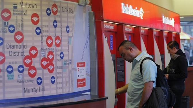 People use an ATM at a Bank of America's branch in New York