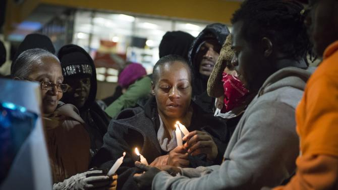 Toni Martin-Green, mother of Antonio Martin, an armed man fatally shot by police late on Tuesday, lights a candle during a vigil for her son in Berkeley