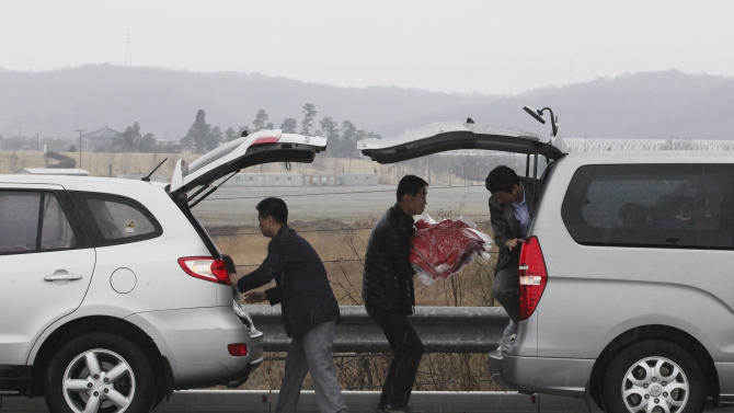 South Korean workers carry clothes,  products from North Korea's Kaesong, from a van to another van after returning from there at Unification Bridge in Paju, South Korea, near the border village of Panmunjom, Saturday, April 6, 2013. Since April 3, North Korean authorities have barred South Koreans from entering North Korea through the Demilitarized Zone to get to the Kaesong industrial complex where some 120 South Korean companies run factories employing North Korean workers. (AP Photo/Ahn Young-joon)