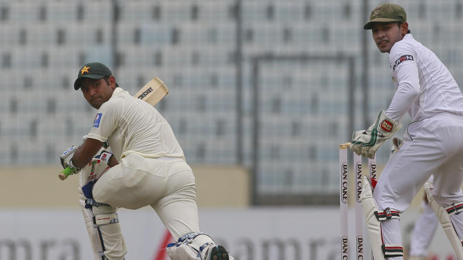 Pakistan's Asad Shafiq, left, plays a shot, as Bangladesh's captain Mushfiqur Rahim watches during the second day of the second test cricket match against Bangladesh in Dhaka, Bangladesh, Thursday, May 7, 2015. (AP Photo/ A.M. Ahad)
