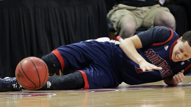 Saint Mary's Jorden Page winces after injuring his knee during the first half of the West Coast Conference tournament championship NCAA college basketball game against Gonzaga, Monday, March 11, 2013, in Las Vegas. (AP Photo/Julie Jacobson)