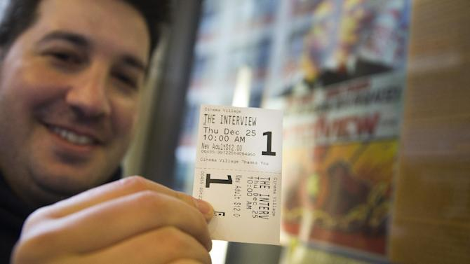 "Derek Karpel holds his ticket to a screening of ""The Interview"" at Cinema Village movie theater, Thursday, Dec. 25, 2014, in New York. The film's Christmas Day release was canceled by Sony after threats of violence by hackers linked to North Korea, but the release was reinstated in some independent theaters and through a variety of digital platforms. (AP Photo/John Minchillo)"