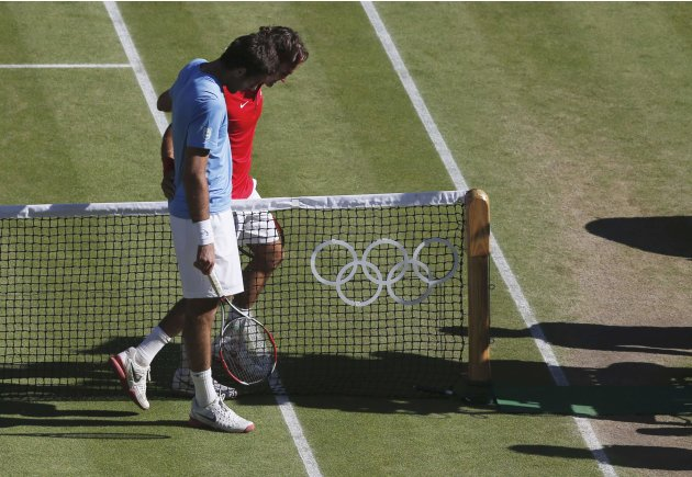 Switzerland's Federer and Argentina's del Potro pat each other on the back after Federer won their men's singles tennis semi-final match at the All England Lawn Tennis Club during the Lond