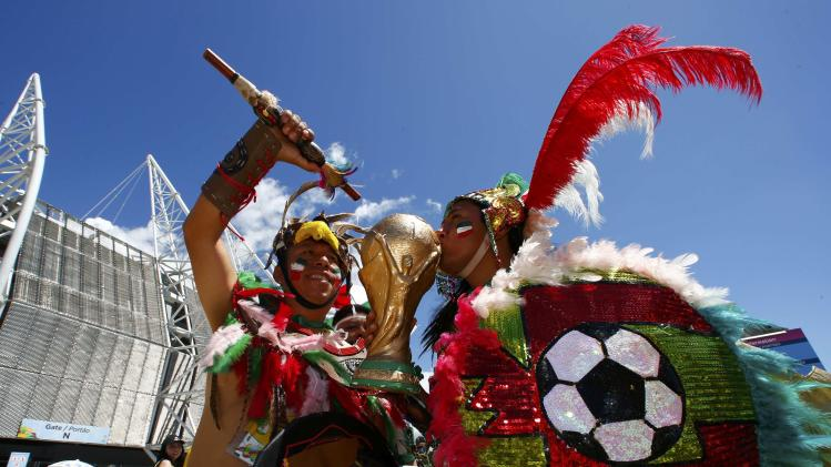 Soccer fans kiss a mock World Cup trophy before the start of the 2014 World Cup round of 16 game between Netherlands and Mexicoat the Castelao arena in Fortaleza