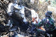 In a photo taken on May 12, an Indonesian soldier searches through the wreckage at the crash site of the Russian Sukhoi Superjet 100 in Mount Salak. Search teams have found an emergency transmitter from the Russian jet that slammed into the dormant volcano in Indonesia
