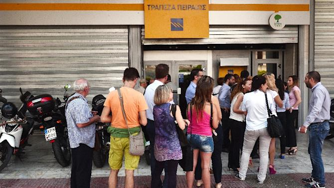 People queue at ATM machines of Piraeus bank in central Athens on June 29, 2015