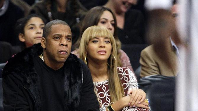 Jay-Z and his wife Beyonce, right, watch the first half of an NBA basketball game between the Brooklyn Nets and the Toronto Raptors, Saturday, Nov. 3, 2012, in New York. (AP Photo/Frank Franklin II)