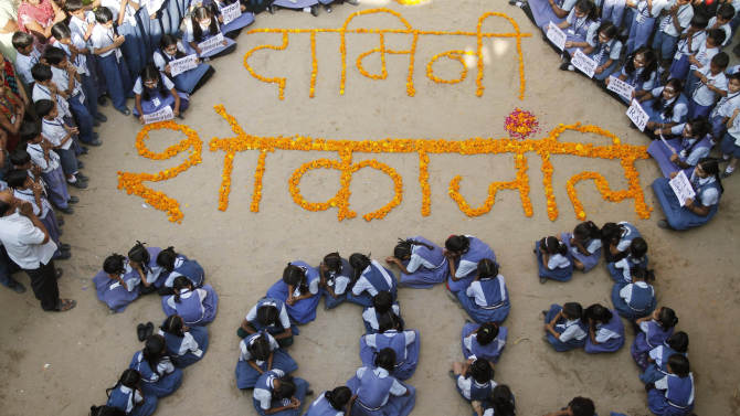 """Indian schoolgirls form numbers representing the year 2013 during a prayer ceremony in Ahmadabad, India, Monday, Dec. 31, 2012. The gang-rape and killing of a New Delhi student has set off an impassioned debate about what India needs to do to prevent such a tragedy from happening again. The country remained in mourning Monday, two days after the 23-year-old physiotherapy student died from her internal wounds in a Singapore hospital. Floral writing at the center reads """"Condolence to Damini,"""" a symbolic name given to the victim. (AP Photo/Ajit Solanki)"""