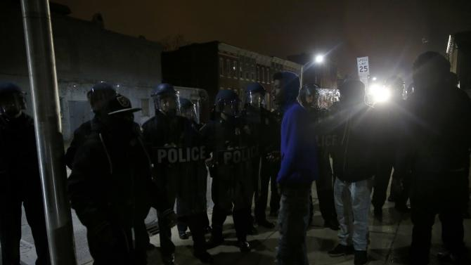 Police stand guard as protesters gather for a rally to protest the death of Freddie Gray who died following an arrest in Baltimore