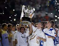 Real Madrid players hold the Spanish League trophy at the Santiago Bernabeu stadium in Madrid on May 13. Champions Real beat Mallorca 4-1 to break the 100-point barrier on the final day of La Liga season