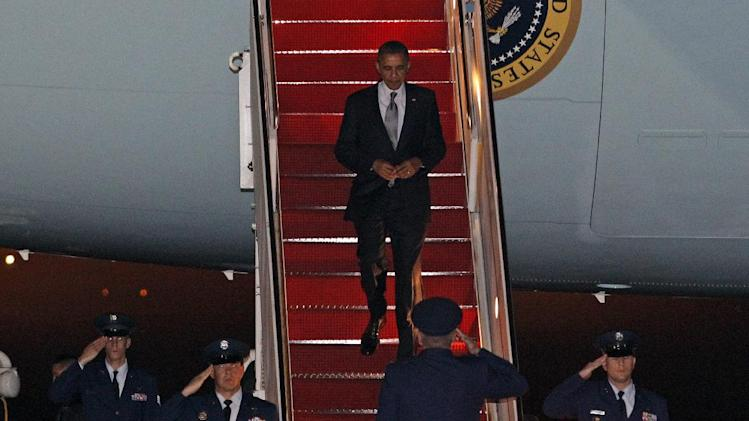 President Barack Obama walks down the stairs from Air Force One upon arrival to Andrews Air Force Base, Md., Saturday, March, 17, 2012. (AP Photo/Jose Luis Magana)