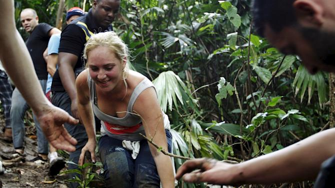 Cuban migrant smiles as she climbs down a slope after she crossed the border from Colombia through the jungle into La Miel, in the province of Guna Yala