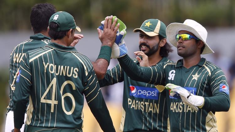 Pakistan's wicketkeeper Akmal celebrates with Alam and Khan after taking the catch to dismiss Sri Lanka's Tharanga during their first ODI cricket match in Hambantota