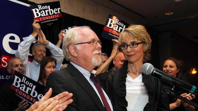 "FILE - In this Tuesday, June 12, 2012 file photo, former Rep. Gabrielle Giffords, D-Ariz., stands with candidate Ron Barber as they celebrate his victory in an election to fill her seat in Tucson, Ariz. Giffords' former district director ran in a special election for the seat she left in January to focus on her recovery from a gunshot wound to the head during a gunman's shooting spree a year earlier. The newly sworn-in congressman, who was also injured in the shooting, held the first ""Congress on Your Corner"" event in the southern Arizona district on Saturday, June 23, 2012 since the incident. (AP Photo/Ross D. Franklin, Pool)"