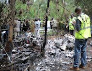 Kenyan forensic experts collect evidence at the site of a police helicopter crash in the Ngong hills outside Nairobi. Kenya's Internal Security Minister George Saitoti was killed Sunday along with five others in the crash. Saitoti, 66, was a candidate in next year's presidential election and a key figure driving his country's fight against Al Qaeda-affiliated insurgents in Somalia