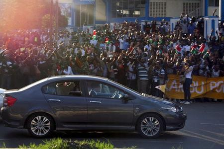 Pope Francis waves to the crowd as he rides in a Honda car within his entourage as he arrives in Kenya's capital Nairobi