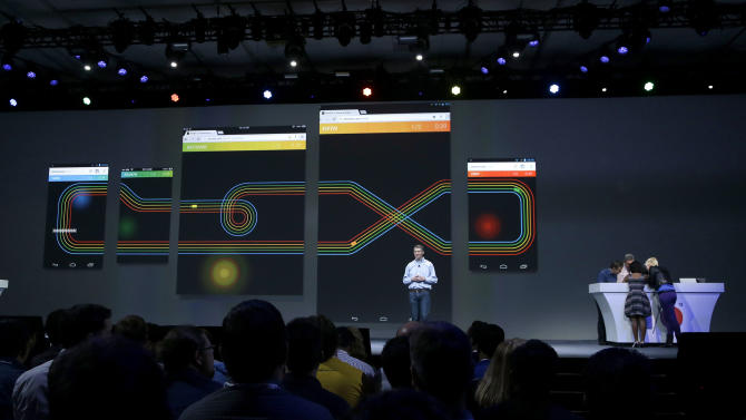 Linus Upson, vice president of engineering at Chrome, speaks as volunteers play Google Racer on different devices at Google I/O 2013 in San Francisco, Wednesday, May 15, 2013. (AP Photo/Jeff Chiu)