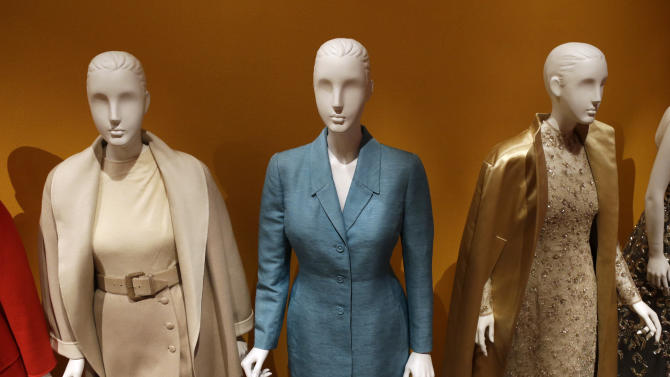 "An Oscar de la Renta pantsuit, center, worn by Former first lady Hillary Rodham Clinton, is displayed next to other creations by the designer at the Clinton Presidential Library in Little Rock, Ark., Monday, July 8, 2013. The ""Oscar de la Renta: American Icon"" exhibit is on display at the Clinton library until Dec. 1. (AP Photo/Danny Johnston)"