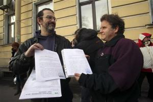 Greenpeace activist Litvinov and Willcox, captain of Greenpeace ship Arctic Sunrise, show papers certifying termination of prosecution in St. Petersburg