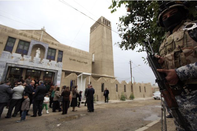 An Iraqi policeman stands guard outside the St. Joseph Chaldean church during a mass on Christmas in Baghdad