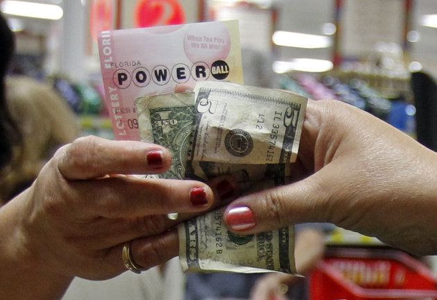 A customer buys three Powerball tickets at a local supermarket in Hialeah, Fla.,Tuesday, Nov. 27, 2012. There has been no Powerball winner since Oct. 6, and the jackpot already has reached a record le
