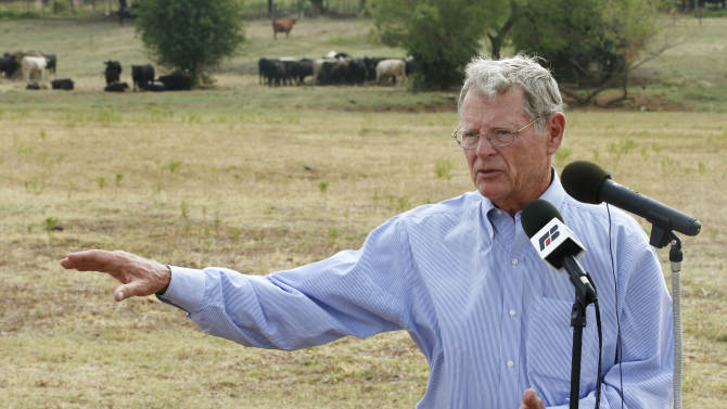 """FILE - In this Aug. 23, 2012, file photo, Sen. James Inhofe, R-Okla., speaks  against the expansion of the Clean Water Act to authority over wet areas on private land in a pasture owned by Gary Johnson in Waukomis, Okla. While the looming fiscal cliff dominates political conversation in Washington, some Republicans and business groups see signs of a """"regulatory cliff"""" they say could be just as damaging to the economy. President Barack Obama has spent the past year """"punting"""" on a slew of job-killing regulations that will be unleashed in a second term, said Inhofe. (AP Photo/Sue Ogrocki, File)"""