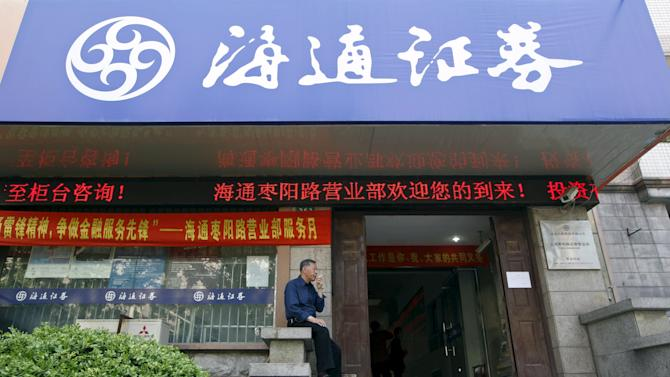 File photo of a man smoking in front of the entrance of a Haitong Securities brokerage house in Shanghai