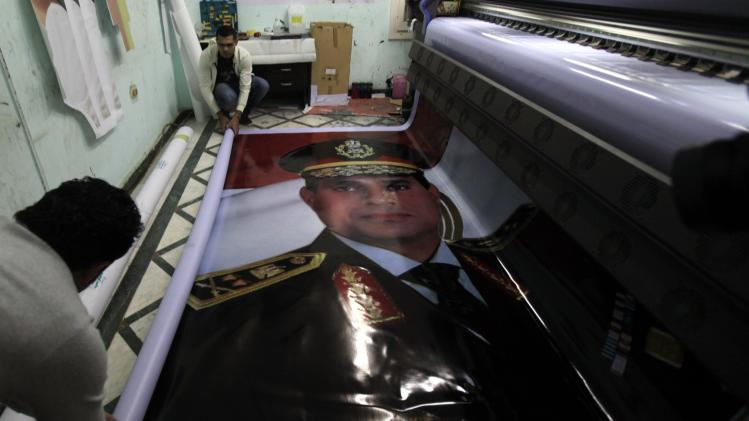 Workers role poster of Egypt's army chief Field Marshal al-Sisi after print it at workshop factory in Cairo