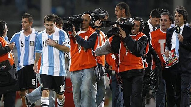 Argentina's Lionel Messi (2nd L) is followed off the field by journalists after they beat Paraguay in 2014 World Cup qualifying (Reuters)