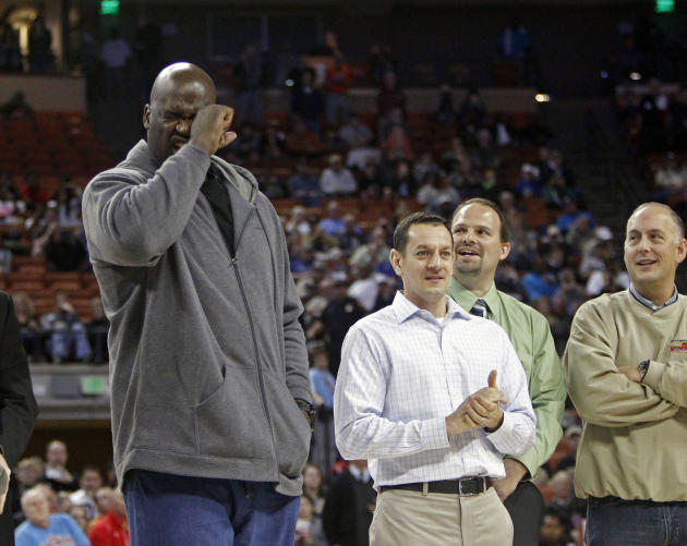 Former NBA star Shaquille O'Neal feigns crying during his introduction while standing with his former high school teammates during halftime of the boys' UIL Class 1A Division 1 state basketbal