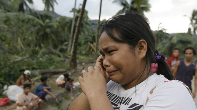 Rosalinda Pasko tearfully breaks the news to a relative of the death of her 2 of her family members at the flash flood-hit village of Andap, New Bataan township, Compostela Valley in southern Philippines Wednesday Dec. 5, 2012. Typhoon Bopha, one of the strongest typhoons to hit the Philippines this year, barreled across the country's south on Tuesday, killing scores of people while triggering landslides, flooding and cutting off power in two entire provinces. (AP Photo/Bullit Marquez)