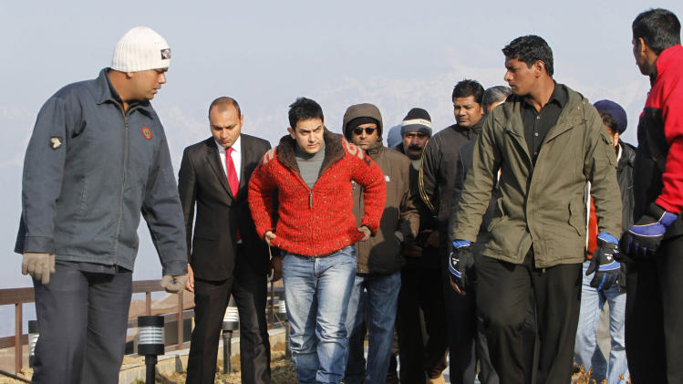 "FILE-In this Feb. 9, 2012 file photo, Bollywood actor Aamir  Khan, third left, arrives at his hotel in Srinagar, Kashmir, India.  Bollywood megastar Khan is making India confront its dark side. Shining light on inequities like the rampant abortion of female fetuses, caste discrimination and the slaying of brides in dowry disputes, actor Khan has reached an estimated one-third of the country with a new TV talk show ""Satyamev Jayate"", or ""Truth Alone Prevails,"" that tackles persistent flaws of modern India that most of its citizens would prefer to ignore.(AP Photo/Javed Ahmad, File)"