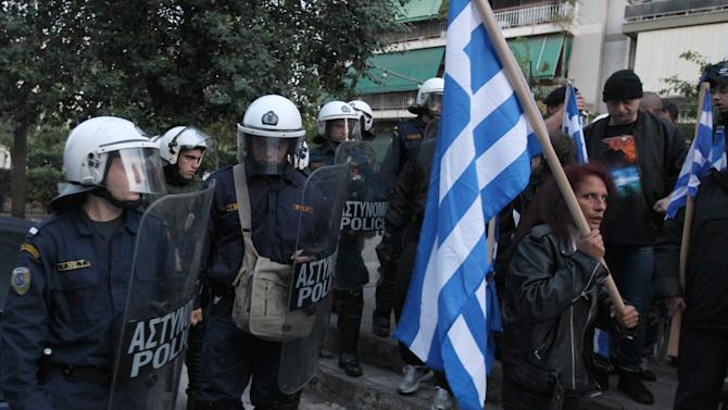 In this image taken  Tuesday, Nov. 16, 2010 riot police look on a residents protest against Muslim immigrants holding outdoor prayers nearby, in this picture taken in central Athens on . Human rights and immigrant groups have warned of a sharp rise in anti-immigrant attacks in Athens in recent months, carried out by far-right groups. In Greece, alarm is rising that the twin crises of financial meltdown and continent-leading illegal immigration are creating the conditions for a right-wing rise _ and the Norway massacre on Monday Aug. 1, 2011 drove authorities to beef up security measures.  (AP Photo/Thanassis Stavrakis)