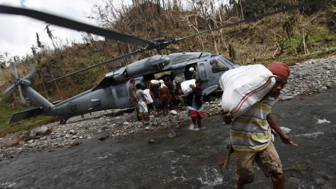 Villagers carry sacks of relief aid as a U.S. helicopter delivers aid to a remote village off Guiuan
