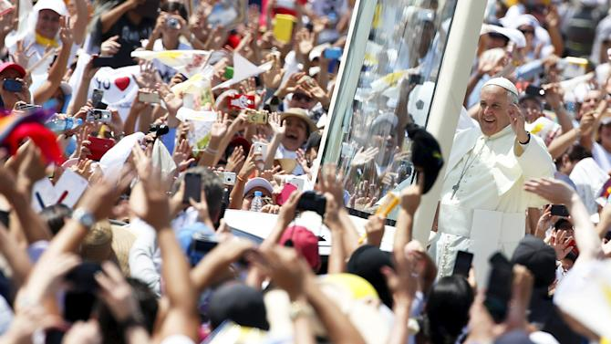 Pope Francis (R) waves as he arrives to lead a mass at the Los Samanes park in Guayaquil