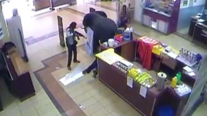 In this frame grab from surveillance video provided by Kenya Police via KTN, a gunman shoots a man trying to take cover inside the Westgate Mall, Sept. 21, 2013, in Nairobi, Kenya. Several attackers from the Somali militant group al-Shabab stormed the mall on Sept. 21, killing at least 67 people during a four-day siege. (AP Photo/Kenya Police via KTN)