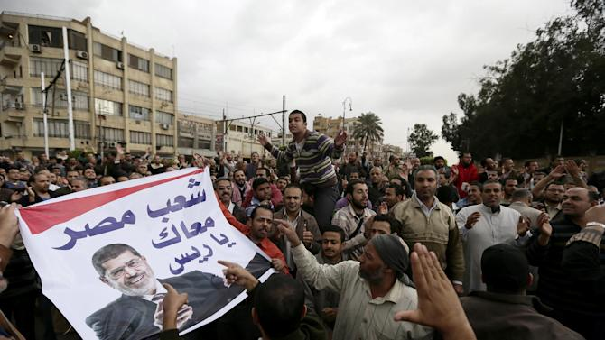 """Supporters of Egyptian President Mohammed Morsi chant slogans during a demonstration outside the presidential palace, in Cairo, Egypt, Wednesday, Dec. 5, 2012. Supporters of Morsi and opponents clashed outside the presidential palace. Wednesdayís clashes began when thousands of Islamist supporters of Morsi descended on the area around the palace where some 300 of his opponents were staging a sit-in. Arabic on the banner reads, """"Egypt's people are with you president."""" (AP Photo/Hassan Ammar)"""