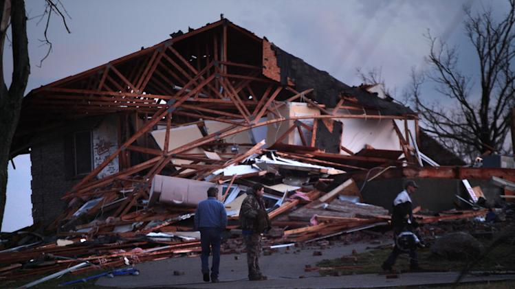 Doug Imhoff, center, stands in front of his home, in Piner KY Friday March 2, 2012 which was only 25% left standing. While the storm was tearing down his house, he was in the basement.  An apparent tornadao swept through the area Friday evening. (AP Photo/The Enquirer, Carrie Cochran)