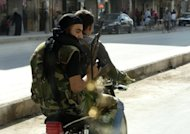 "Syrian rebels armed with their AK-47 ride a motorcycle in the northern city of Aleppo. Regime aircraft hammered insurgent bastions nationwide on Sunday as rebels said they now control most of the country and have moved their command centre from Turkey to ""liberated areas"" inside Syria"