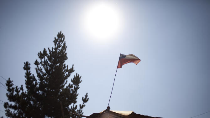"""A Chilean flag waves on top of a house at the San Pablo shanty town in Santiago, Chile, Wednesday, Jan. 23, 2013.  European, Latin American and Caribbean leaders gathering for this weekend's economic summit will likely see only one side of Chile _ the polished, upscale country where tourists and investors stay in five-star hotels in a sparklingly clean financial district nicknamed """"Sanhattan,"""" well away from Santiago's slums. (AP Photo/Victor R. Caivano)"""