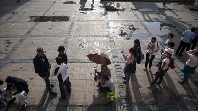 Voters line up at a polling station during the presidential election at Candelaria square in downtown Caracas, Venezuela, Sunday, Oct. 7, 2012.  President Hugo Chavez is running for re-election against opposition candidate Henrique Capriles. (AP Photo/Sharon Steinmann)