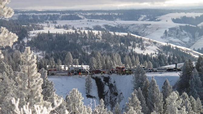 Emergency personnel respond to the scene of a multiple fatality accident where a tour bus careened through a guardrail along an icy Oregon highway and several hundred feet down a steep embankment, authorities said, Sunday, Dec. 30, 2012 about 15 miles east of Pendleton, Ore. The charter bus carrying about 40 people lost control around 10:30 a.m. on the snow- and ice-covered lanes of Interstate 84, according to the Oregon State Police. (AP Photo/East Oregonian, Tim Trainor)