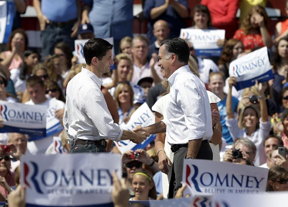 Republican presidential candidate, former Massachusetts Gov. Mitt Romney, right,  and his vice presidential running mate, Rep. Paul Ryan, R-Wis., shake hands during a campaign event at the Long Family Orchard Farm and Cider Mill in  in Commerce Township, Mich., Friday, Aug. 24, 2012, (AP Photo/Paul Sancya)