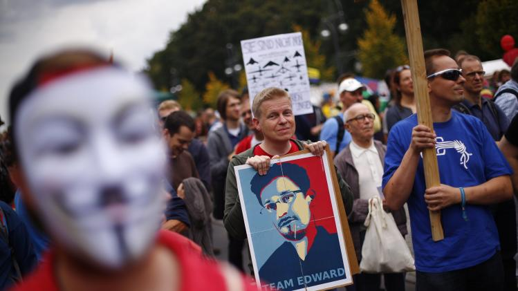 Man holds placard with portrait of former US National Security Agency contractor Snowden during protest calling for protection of digital data privacy in Berlin