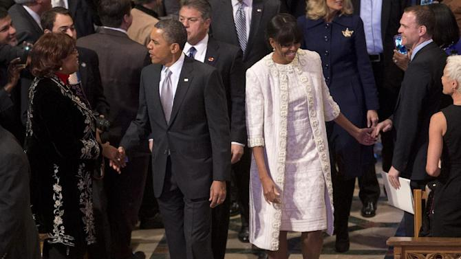 President Barack Obama and first lady Michelle Obama greet people as they arrive for the Presidential Inaugural Prayer Service at the Washington National Cathedral in Washington, Tuesday, Jan. 22, 2013. The 106-year-old Episcopal church has long hosted presidential inaugural services., this one following Monday's 57th Presidential Inauguration.  (AP Photo/Carolyn Kaster)
