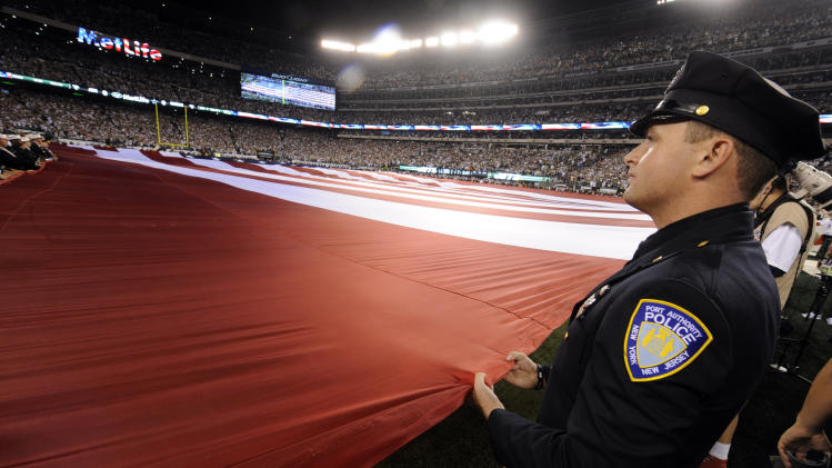A Port Authority of New York and New Jersey police officer holds the American flag during the playing of the national anthem before an NFL football game between the Dallas Cowboys and New York Jets, Sunday, Sept. 11, 2011, in East Rutherford, N.J. (AP Photo/Henny Ray Abrams)