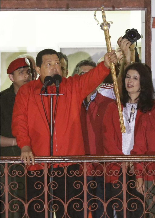 Venezuela's President Hugo Chavez, left,  hods up ta replica of Simon Bolivar's sword  as he greets supporters from the Miraflores presidential palace balcony in Caracas, Venezuela, Sunday, Oct. 7, 20